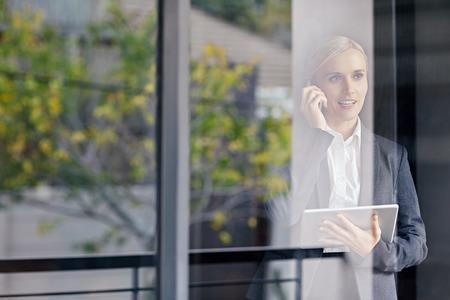 Une jeune femme d'affaires travaillant Aperçu à travers sa fenêtre de bureau