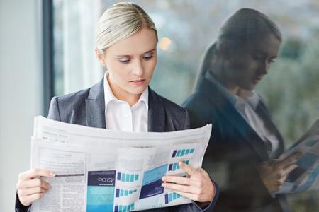 Une jeune femme d'affaires la lecture de la newpaper en dehors de son bureau