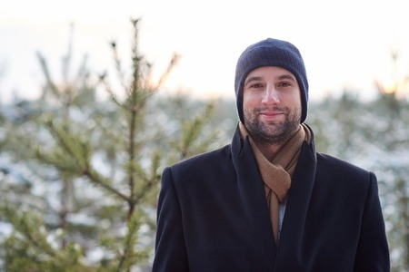Portrait of a man with stubble, wearing a beanie and coat on a cold winter day, looking at the camera with a warm smile and positive expression, with a young green tree growing behind him