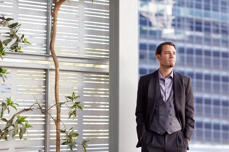 deep thought: Creative businessman in a stylish suit, looking away in deep thought, while standing in a city environment, next to a screen that has a plant growing against it