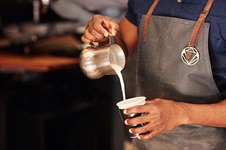 Geerntetes Bild eines afrikanischen Barista sorgfältig gießt Milch aus einem Edelstahl-Krug in ein Essen zum Mitnehmen Tasse in einem Café Standard-Bild - 54728021