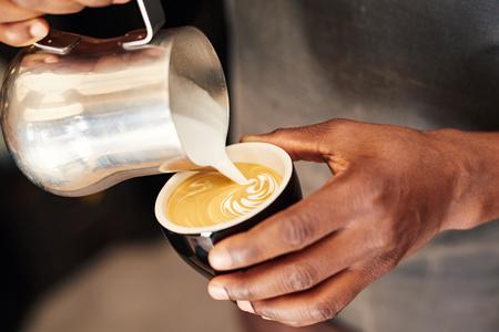 Handen van een geschoolde Afrikaanse barista die schuimende melk uit een roestvrijstalen kruik gooien in een keramische koffiekopje en een aantrekkelijk patroon vormt op de top van de cappucino, maakt hij druk Stockfoto
