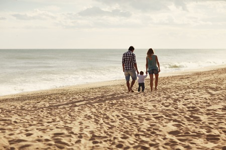 Couple and their toddler walking away from the camera along a peaceful beach
