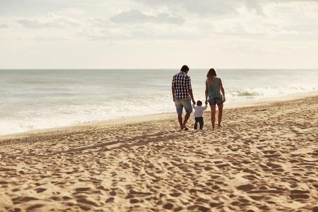 Couple et leur enfant en bas âge à marcher loin de la caméra le long d'une plage paisible