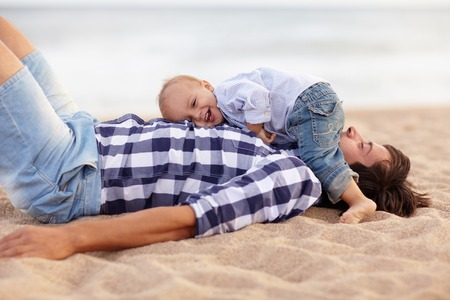 Cute little baby boy lying on his dads chest and laughing out loud at the beach