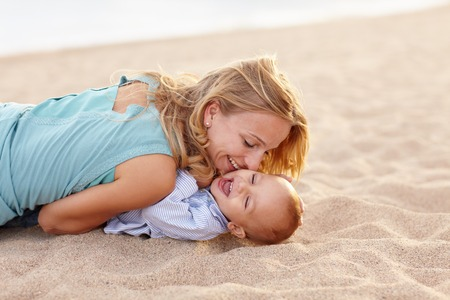 Beautiful young mother playing with her laughing baby son on the beach