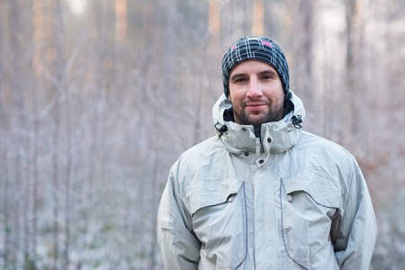 Portrait of a handsome man with rugged stubble, wearing warm clothes while standing outdoors on a cold winter day, looking at the camera with a subtle smile and a snowy forest behind him 版權商用圖片