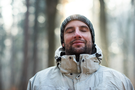 Head and shoulders portrait of a man in a winter jacket and beanie, standing outdoors on a cold day in a forest with his eyes closed and a subtle smile on his lips, feeling absolutely peaceful