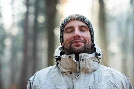 Kopf und Schultern Porträt eines Mannes in einer Winterjacke und Mütze, stand im Freien an einem kalten Tag in einem Wald mit geschlossenen Augen und einem feinen Lächeln auf den Lippen, das Gefühl, absolut ruhig