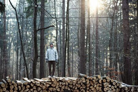 tronco: Retrato de cuerpo entero de un hombre que llevaba ropa de abrigo en un día de invierno en un bosque con la luz del sol suave, de pie sobre troncos de árboles para leña dividido que se apilan en una pila larga