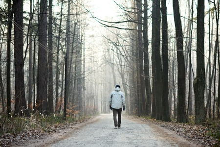 Achteruitkijkspiegel volledige lengte shot van een man lopen weg van de camera langs een weg door een bos in de winter