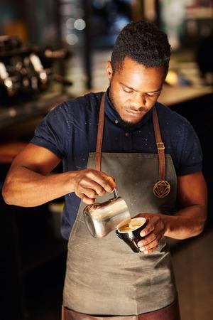 High Angle oog van een knappe Afrikaanse man zorgvuldig gieten schuimende melk uit een roestvrij stalen kan in een cappucino, in de coffeeshop, waar hij werkt als een barista Stockfoto