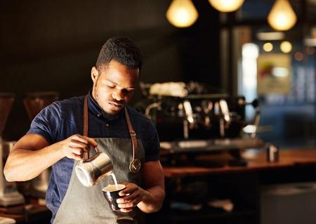 Knappe Afrikaanse man gieten geschuimde melk voorzichtig in een cappucino, met een zachte 's ochtends licht en een moderne koffieshop achter hem, waar hij een baan als een barista