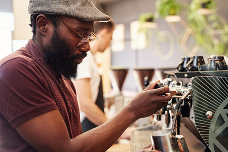occupations: Hansome African man with a beard and hipster style, using a modern espresso machine to froth milk in a coffee shop
