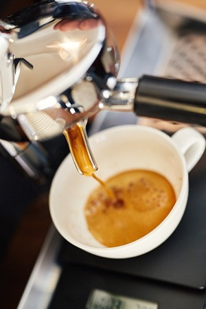 High angle closeup view of a shiny metal portafilter attached to an espresso machine with fresh coffee pouring out in a ceramic cup