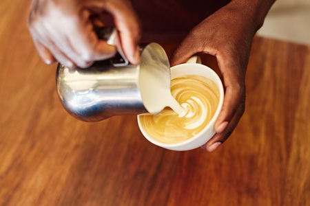 foamed: Cropped closeup of the hands of an african barista carefully pouring foamed milk from a stainless stell jug, into a coffee cup to form a fancy pattern on a cappucino Stock Photo