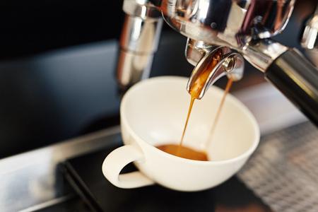 에스프레소 기계에 반짝이 금속 포터 필터에서 화이트 세라믹 컵에 붓는 신선한 커피의 근접 촬영
