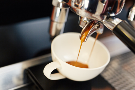 Closeup of fresh coffee pouring into a white ceramic cup from the shiny metal portafilter on an espresso machine