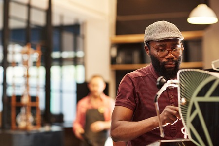 Handsome Afro-American man in hipster cap and spectacles, making coffee at an espresso machine in a modern coffee shop photo