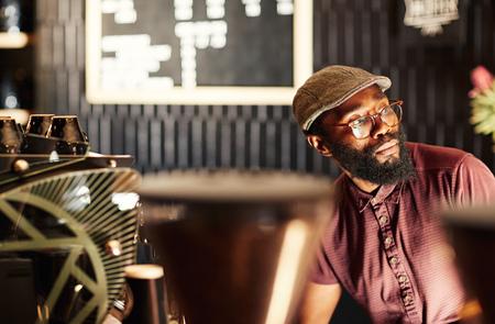 人像一個時髦的非洲男子與時髦風格的鬍子,眼鏡和帽子,坐在現代化的咖啡廳,望著遠處在深思,用柔和的燈光落在他的臉上 版權商用圖片 - 54728198