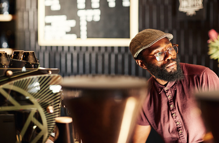 Portrait of a fashionable African man with a hipster style beard, spectacles and cap, sitting in a modern coffee shop and looking away in deep thought, with gentle light falling on his face photo