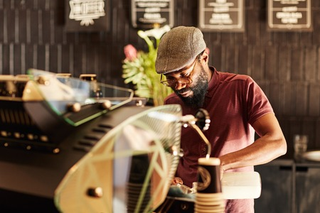 Handsome African man with a hipster style, working behind an espresso machine in a modern coffee shop where he has a job as a barista photo