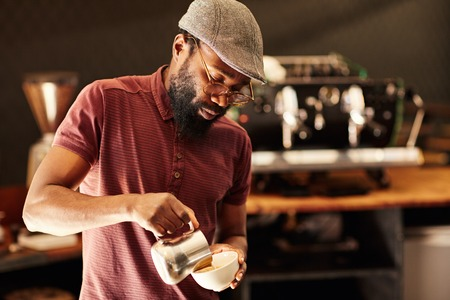 Handsome African barista with spectacles and a stylish cap, pouring milk into a cappucino in a modern coffee shop 版權商用圖片