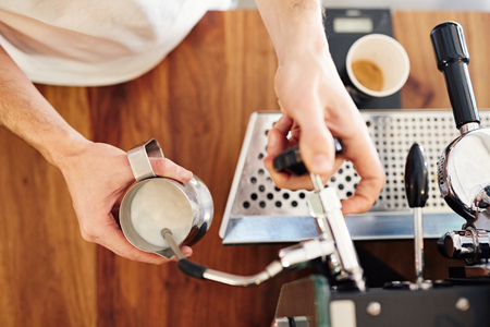baristas: Overhead shot of a baristas hands using an espresso machine to steam some fresh milk in a stainless steel jug
