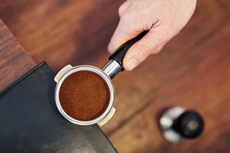 espresso machine: Overhead shot of a persons hand holding the handle of shiny new portafilter for an espresso machine containing a perfectly level amount of fresh ground coffee, with a tamper visible on counter below