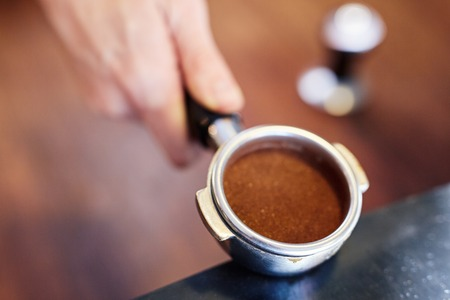 differential focus: Cropped closeup shot of a shiny new portafilter containing freshly ground coffee neatly packed into it, with differential focus Stock Photo