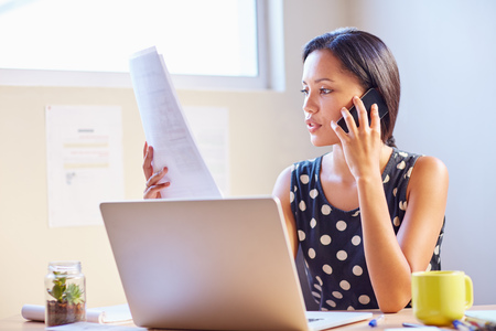 female business: A young businesswoman talking on the phone while looking at a document