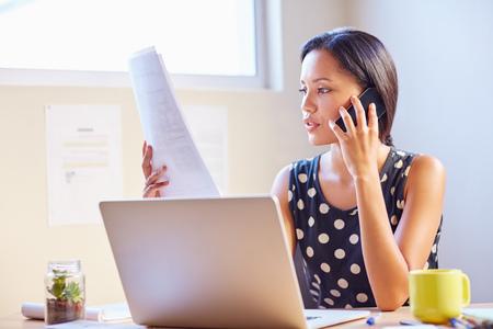 Eine junge Geschäftsfrau am Telefon zu sprechen, während in einem Dokument suchen Standard-Bild