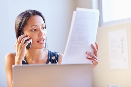 business casual: A young businesswoman talking on the phone while looking at a document