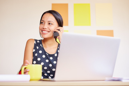 work from home: A young businesswoman talking on the phone while sitting in front of her laptop