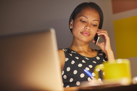 laptop home: A young businesswoman talking on the phone while sitting in front of her laptop at night Stock Photo