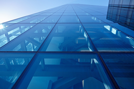 infrastructure buildings: Abstract closeup of the glass-clad facade of a modern building covered in reflective plate glass