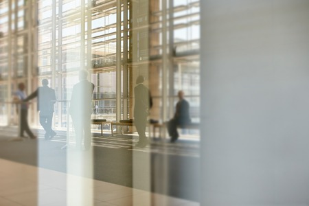 corporate buildings: Abstract images of real businesspeople in motion through glass in a busy conference centre