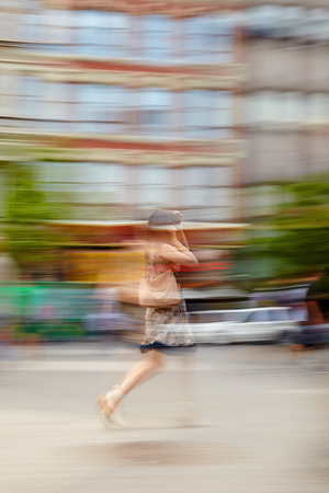 citylife: Blurred motion image of a woman walking down a city street Stock Photo