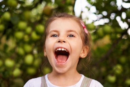 boca abierta: Retrato de una niña linda que hace una cara emocionada con la boca abierta