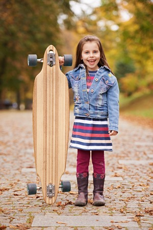 longboard: Cute little girl standing alongside a longboard skate board outdoors
