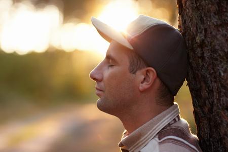 hombre orando: foto de perfil de un hombre joven con los ojos cerrados meditabundo en un bosque temprano por la mañana Foto de archivo