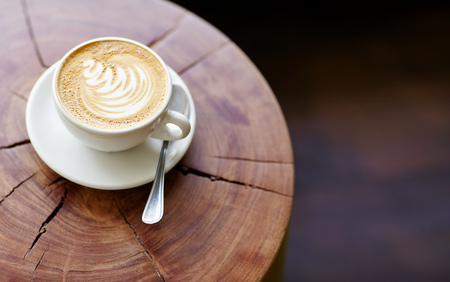 fairtrade: Closeup of a cappucino on a wooden stump with beautiful natural patterns