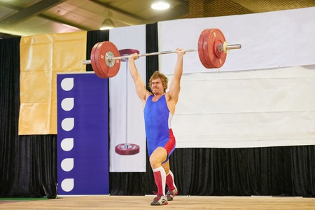 snatch: A weight lifter lifting weights during a competition Stock Photo