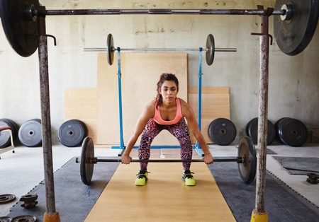 levantando pesas: Hermosa mujer en un gimnasio levantando pesas privados de manera enfocada y seus Foto de archivo