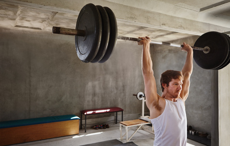 muscle toning: Wide angle shot of a strong man lifting very heavy training weights in a private gym