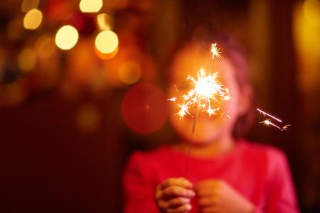 Une petite fille heureuse de jouer avec un sparkler