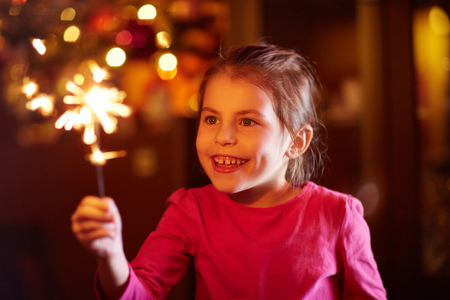 child smile: A happy little girl playing with a sparkler Stock Photo