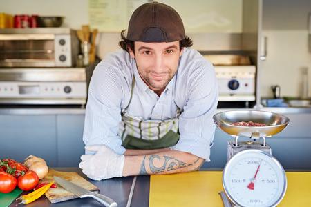 Eten ondernemer op zoek blij met zijn nieuwe top-kwaliteit gehakt hamburger vlees dat hij een gewicht van een retro keukenweegschaal