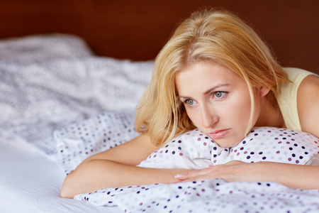 beautiful sad: A young woman looking worried while lying in bed