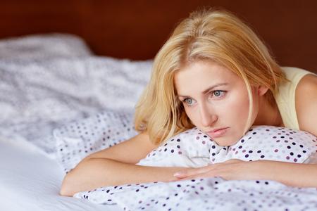 mujer triste: Una mujer joven con cara de preocupación mientras está acostado en la cama